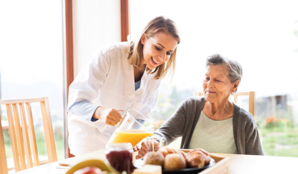 caregiver preparing breakfast for elderly woman